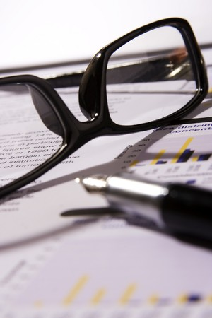 A Financial statement with a black frame eyeglasses and fountain pen.