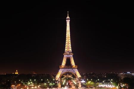파리, 프랑스 - 2010 년 4 월 01 일 : 에펠 탑의 긴 노출은 세느 강을 건너에서 볼. 사진은 타워가 밤에 어두운 하늘을 대조의 따뜻한 조명과 함께 조명 쇼