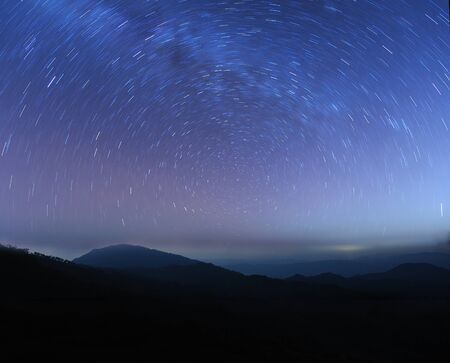 astrophotography: Longtrail star in the sky over mountain Stock Photo