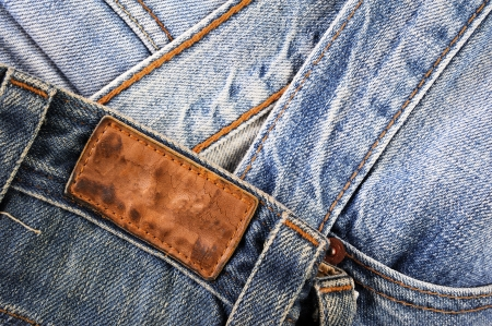 zigzagger: Old blank leather label on blue jean Stock Photo