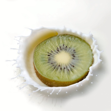 Fresh kiwi falling into the milk with a splash closeup