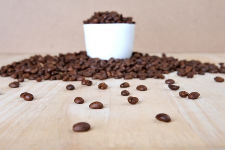 Fresh coffee beans on wood and linen bag, ready to brew delicious coffee photo