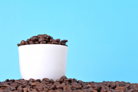Fresh coffee beans on blue background photo