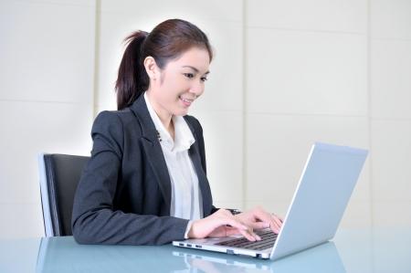 사무실에서 노트북을 사용하는 비즈니스 여성 스톡 콘텐츠