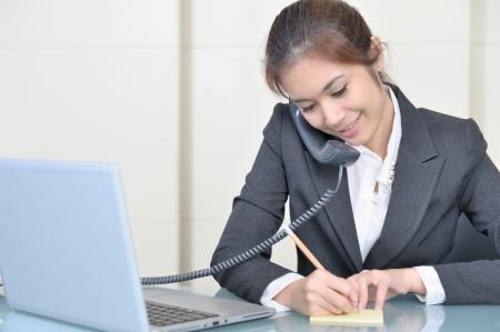 secretaries: Se�ora hermosa joven hablar de negocios con el tel�fono