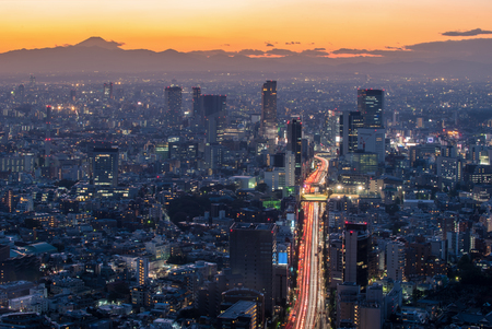 megacity: The sun sets over the cityscape of Tokyo, with Mount Fuji.