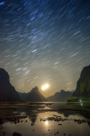 trailing: Milford sound at night with startrail, New Sealand Stock Photo