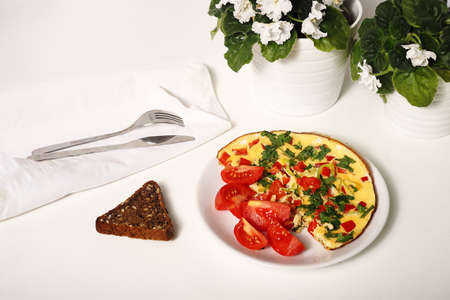 omelette with a wedge of bread with cutlery on white background