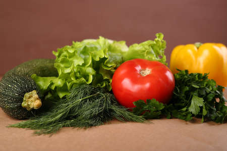Vegetables - dill salad tomato pepper squash on brown background. 免版税图像