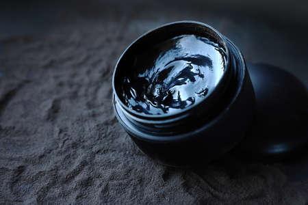 Black jar with black gel on black powder. Facial care products.