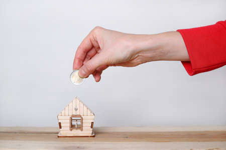 Wooden house and hand with a coin - euro. Buying a property