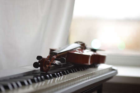 Red violin on the keyboard of the electronic piano on the background of the window