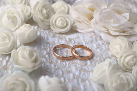 Gold wedding rings on beige fabric decorated with beige artificial flowers