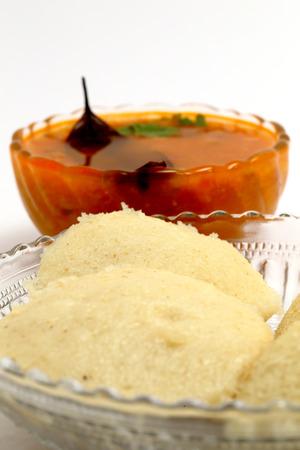 material de vidrio: Idli - sambhar una comida india normalmente realizado en el sur de la India, pero querido y preparado casi en todas partes de la India, muy bien presentado en una cristaler�a, aislado en blanco