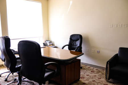 An interior view of modern office with chairs and glass-top table, telephone and other booklets. Archivio Fotografico