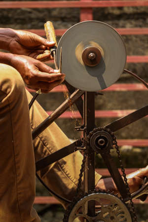 A metal worker sharpening a cutting tools with his locally made equipment. Banco de Imagens