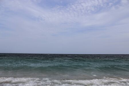 Blue ocean water and waves showing horizon at the far end. View  of vast ocean from a shore.
