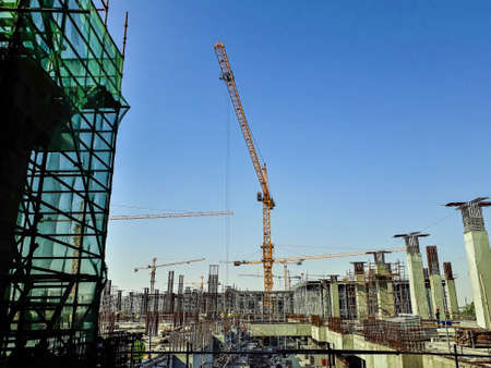 Doha, Qatar- November 8 2018: Construction site of a big shopping mall in Doha, Qatar showing cranes, lifters, concretes, buildings, heavy machineries and steel frameworks. Publikacyjne