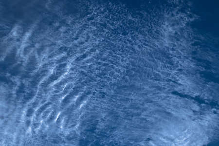 Beautiful blurry pattern of intermittent and scattered clouds on a sunny day with the blue sky as background. Bluish sky color as abstract background or backdrop.