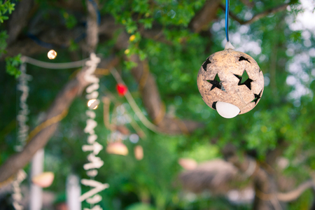 The flashlight and the shade of coconut with asterisks on the tree decoration for the lamp on the beach of a tropical island, Indonesia