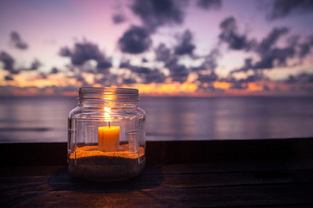 beeswax candle: Candle lamp on wooden table with sea and sunset background, romantic dinner in the restaurant. Indonesia Bali Stock Photo
