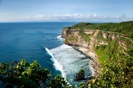 Panoramic view of the ocean with waves with a high cliff on a Sunny day with clouds. Uluwatu, Bali