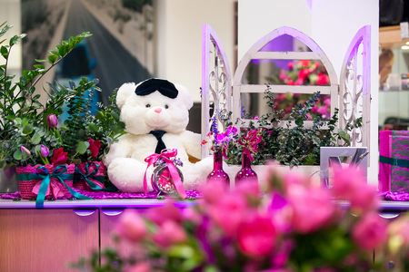 Decorative white bear in the interior against the vases and flowers, papier mache