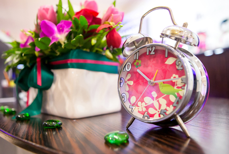 Decorative pink alarm clock in the interior against the basket and flowers, papier mache