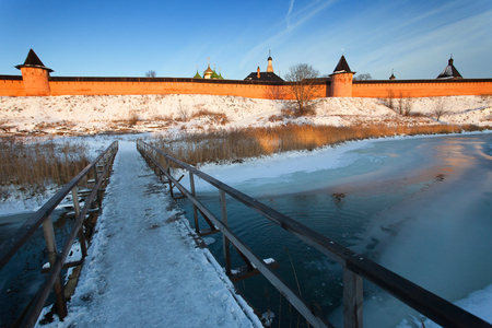 Winter landscape in the early frosty morning in Suzdal. Wooden bridge across the river Kamenka on the background of the temples and buildings of the Kremlin