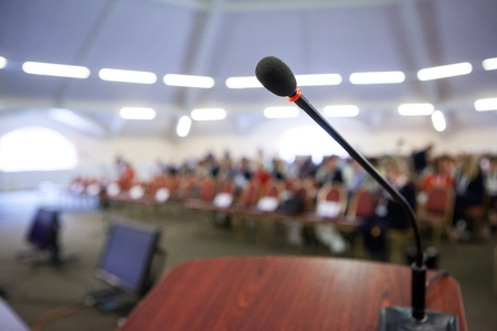 Speech or conference concept. Microphone on stand in front of audience. Stock Photo