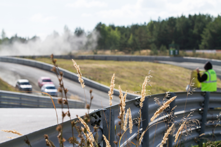 Racing rally-cross and crash barriers, focus on the dry grass on the background of cars