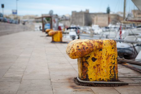 Old yellow bollard in the port