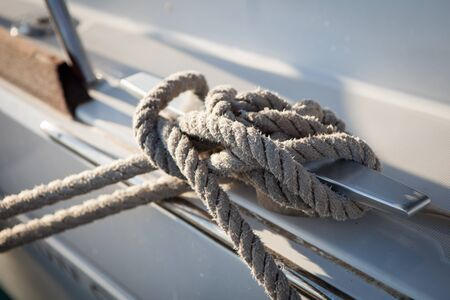 fixed line: White mooring rope tied around steel anchor on boat or ship