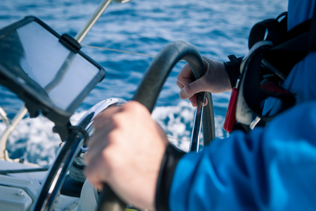 timon barco: Hands of the skipper at the helm control of sailing boat