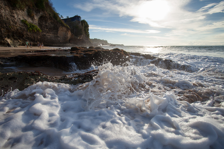 Ocean wave with foam beating against the rocks at sunset
