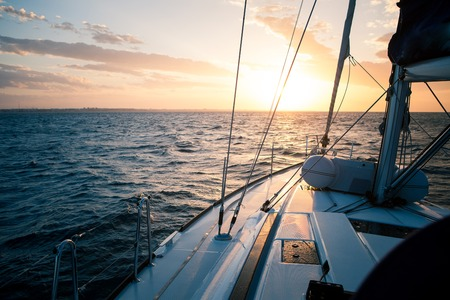 tilting: Sailing yacht at sunset in the open sea