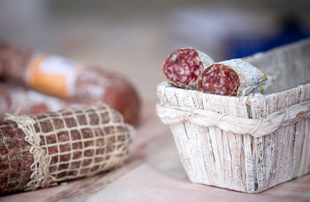 Traditional home-made salami in the basket on the market for sale.