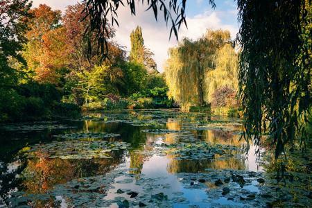 Claude Monet el jardín en otoño, lirios de agua en el lago en un día soleado