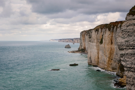 manche: The beach and cliffs of Etretat with a gloomy sky, tourist site of a Norman French town Stock Photo