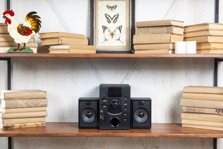 Compact music center in vintage residential loft interior on the shelf among books and accessories
