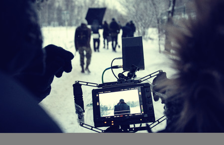 Shooting a feature film, backstage on the set in the street in the winter, the view from the camera. The work of the cameraman. Toned photo