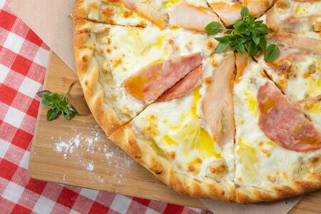 Pizza with different sausages close-up with different ingredients decorated with Basil, an assortment of traditional Italian fast foods