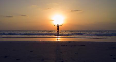 Goa, India. Man dancing on the stilts. Sunset on the beach.