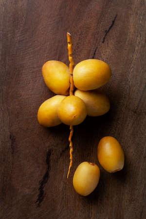 yellow fresh dates fruit isolate on wooden background