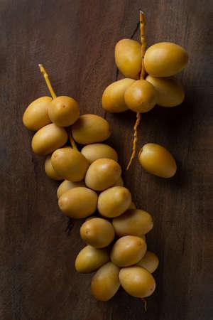 fresh yellow dates isolate on wooden background 免版税图像