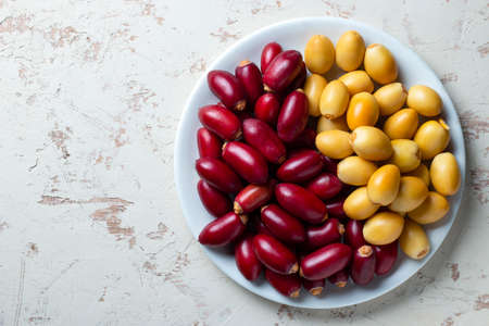 red and yellow fresh dates fruit in white plate 免版税图像
