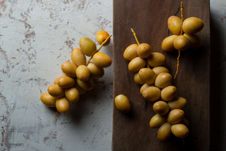 fresh yellow dates on wooden background