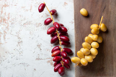 fresh yellow and red dates on wooden background