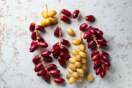 red and yellow fresh dates fruit bunch on white background 스톡 콘텐츠