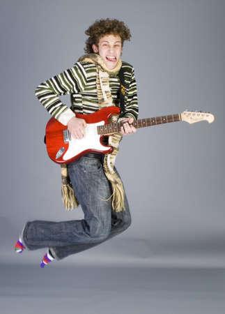 孤立した背景の上のギターと美しい若い男